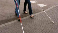Görme engelli bir kişi kırmızı – beyaz renkli baston taşıyor